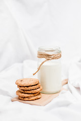 Photo of a milk and cookies on a small wooden board