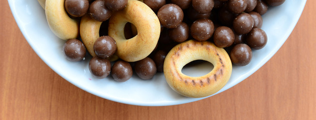 Crispy tubules, chocolate melting balls and bagels lie in a white plate on a wooden table. Mix of various sweets