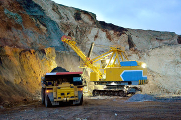 Excavator loads rock in the dumper