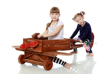 two sisters playing in a wooden plane