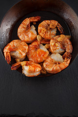 fresh prepared king prawns in an iron pan with garlic on dark slate kitchen plate can be used as background