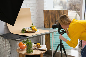 Young woman taking picture of lemons, mint and ginger in professional studio. Food photography