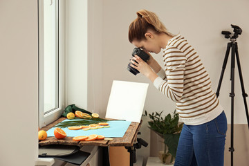 Woman taking picture of cut fruits and palm leaf on window sill. Food photography