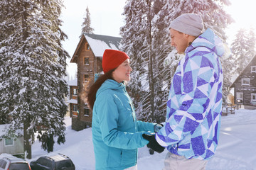 Happy couple at beautiful snowy resort. Winter vacation