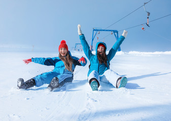 Happy women sliding down the snowy hill. Winter vacation