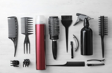 Flat lay composition with professional hairdresser tools on wooden background