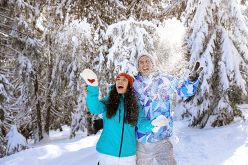 Happy couple having fun in snowy countryside. Winter vacation