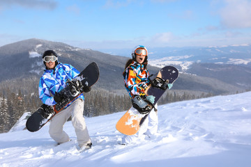 Couple with snowboards having fun on ski piste at snowy resort. Winter vacation