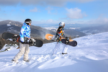 Couple with snowboards on ski piste at snowy resort. Winter vacation