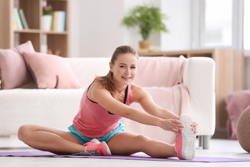 Beautiful young woman doing fitness exercise at home