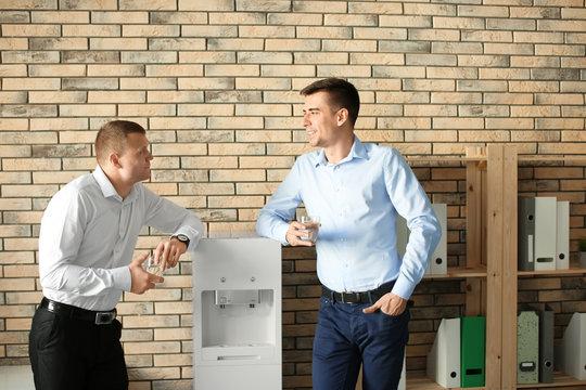 Office employees having break near water cooler