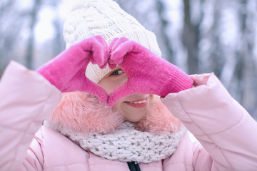 Cute girl showing heart on frosty day outdoors. Winter vacation
