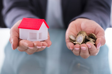 Businessperson Holding Coins And House Model