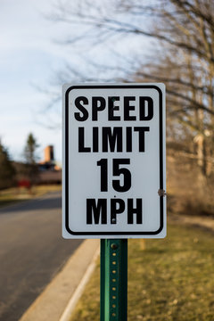 Speed limit sign 15 mph in a peaceful neighborhood in spring