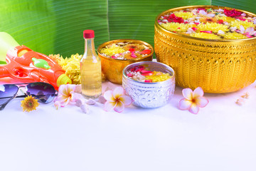 Thai traditional jasmine garland and Colorful flower in water bowls decorating and scented water, perfume, marly limestone, pipe gun for Songkran Festival or Thai New Year