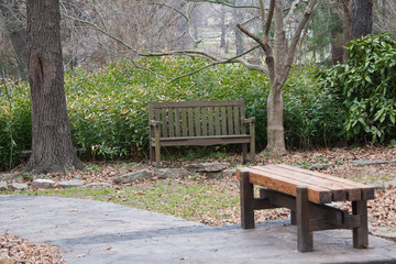 Two benches placed near an outdoor walking path.