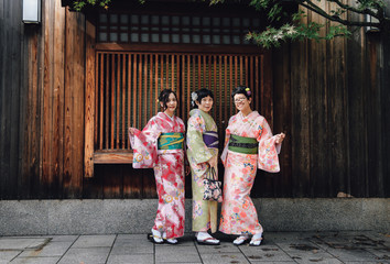 Group of woman friends in traditional Japanese dress, kimono, take a picture together at Gion district, Kyoto, Japan.