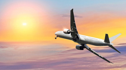 Commercial airplane flying above beautiful sky in dramatic sunlight.Travel and transportation concept.