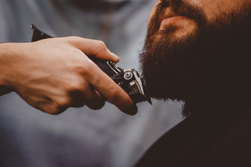 Man with beard client in barbershop hairdresser on shaving with dangerous razor.