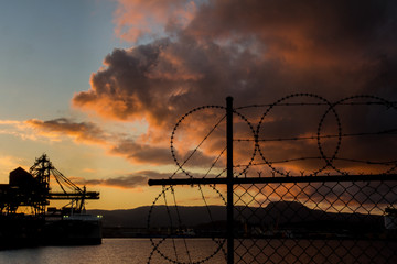 Industrial Shipping port view through razor wire with approaching evening storm