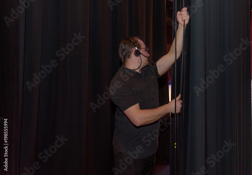 Male Theater Technician Pulling A Curtain Pulley