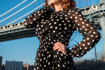 Female wearing black and white polka dots dress posing outdoors in the city
