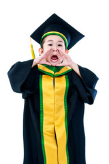 Asian child in graduation gown holding hands near to open mouth.