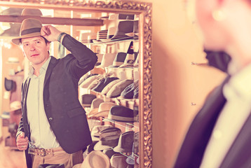 customer try on brim hat and looking in mirror at dressing room