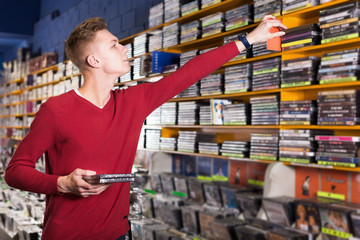 Serious young man absorbedly choosing CD and DVD