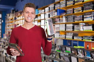Spoed Foto op Canvas Muziekwinkel Portrait of smiling young man with stack of DVDs in hands