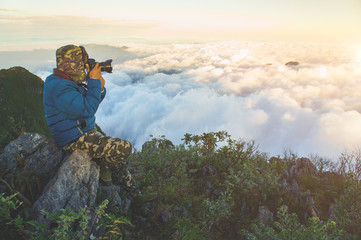 The Photographer is taking a picture of sunrise in mountains wiht fog