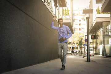 Businessman walking trough street holding digital tablet and say hi someone.