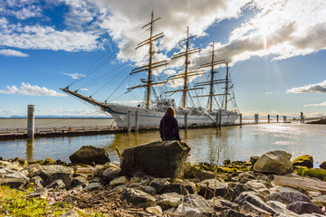girl sits on a rock and looks at the big white sailing ship moored to the pier