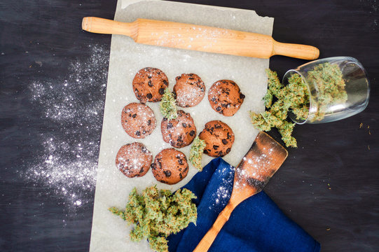 Cookies with cannabis and buds of marijuana on the table. Concept of cooking with cannabis herb. Treatment of medical marijuana for use in food top view, On a black background