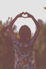 Girl holding a heart-shape with hands in nature.
