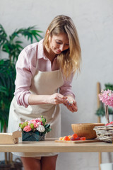 Portrait of young blonde florist composing bouquet of marshmallows, flowers
