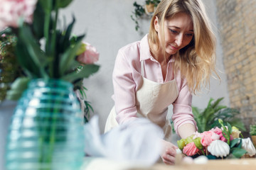 Photo of florist making bouquet at table