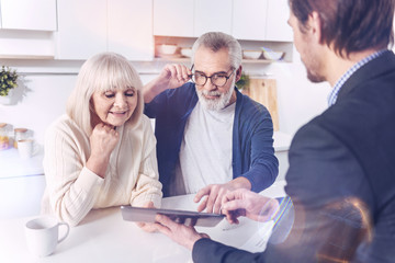 Just have a look. Positive elderly couple looking at the screen of tablet while talking with their real estate agent and meeting in the kitchen