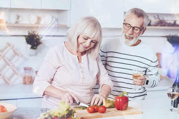 Healthy lifestyle. Cheerful delighted aged couple standing in the kitchen and making vegetable salad while expressing gladness