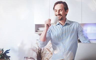 Pleasant morning. Cheerful delighted man drinking coffee and enjoying time while getting ready to go to work