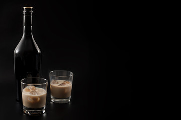 Coffee liqueur and alcoholic beverages based on milk and whiskey concept with Irish cream bottle and glasses with ice isolated on dark black background with copy space Fototapete