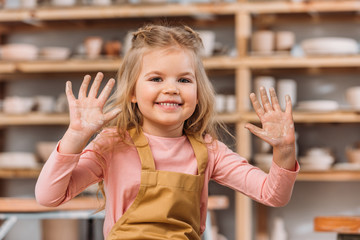 adorable smiling child showing hands in clay