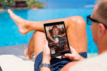 Man reading emagazine on vacation by the pool
