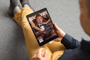 Man reading magazine on tablet