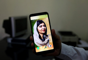 A man holds his mobile phone with a digital image of Nobel Peace Prize winner Malala Yousafzai at Khushal School in her home district in Swat Valley