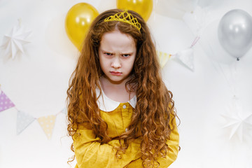 Emotional princess girl with angry expression on face in birthday party.