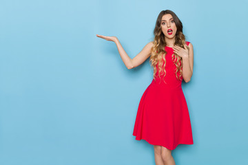 Surprised Elegant Young Woman In Red Dress Is Presenting