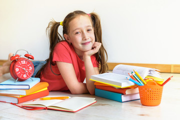 Homeschooling. The child, the pupil, the schoolgirl lies on a floor with a pile of books and writes homework. Education of children. Training of children in kindergartens and schools.