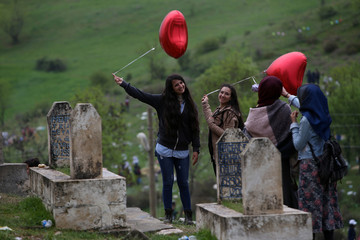 Women pose with balloons for a souvenir picture near the tomb of Islamic saint Muaz bin Cebel during the annual Ser Hivde gathering, a religious festival to wish good fortune, in Kumgolu in Silvan