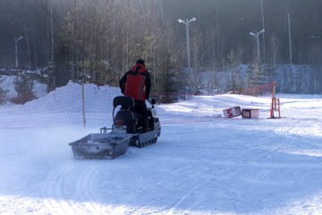 Man driving sports snowmobile in Finnish Lapland in a sunny day .